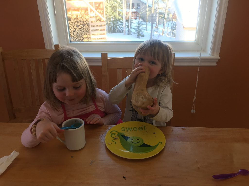 two kids drinking bone broth and sucking the marrow out of bones.