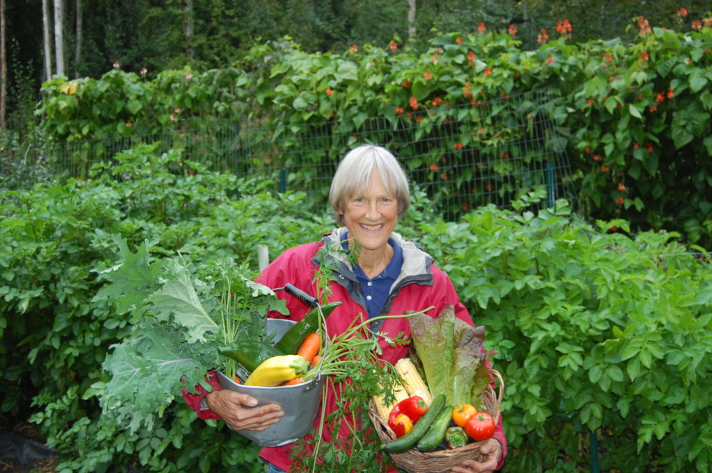 Terry Riechardt poses with two baskets of vegetables from her garden.
