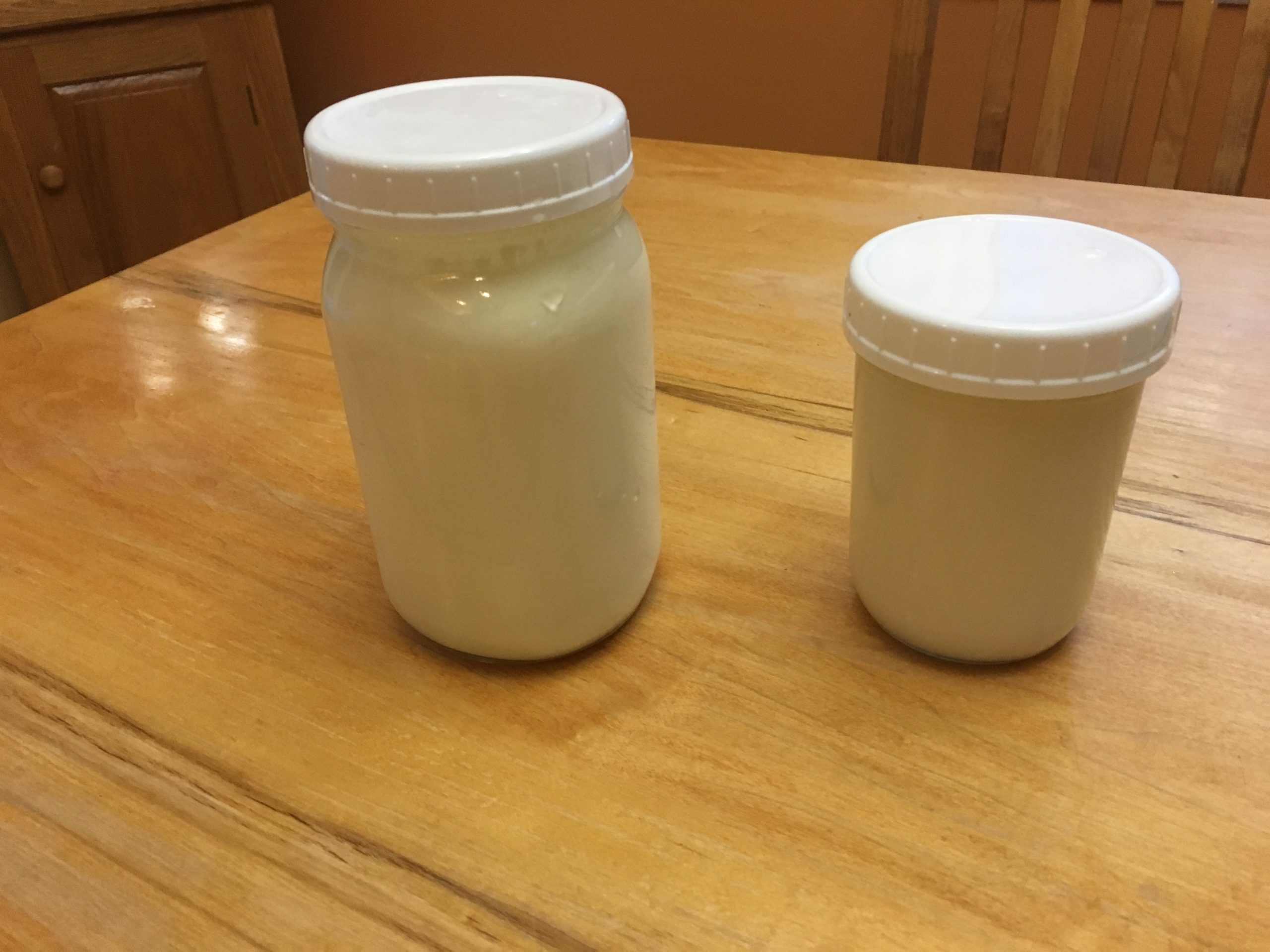 A pint-sized jar of homemade cream friach next to a quart-sized jar of yougurt.