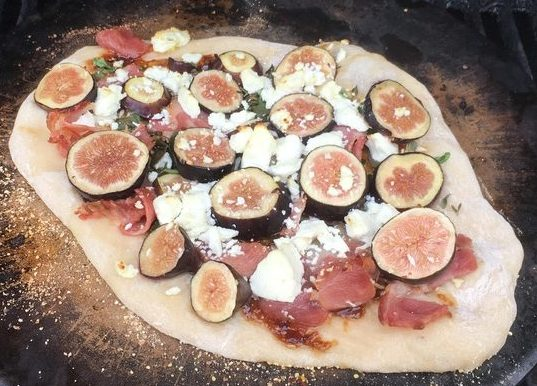 a pizza with round circles on it (fresh figs) and white cheese (goat cheese)