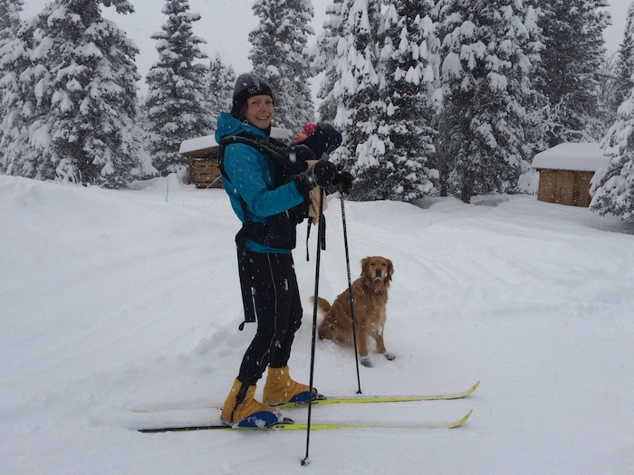 heidi cross country skiing with dog and baby with snow falling